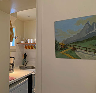 Inside kitchenette with dishes, coffee maker, fridge, and sink.  Mountain painting.