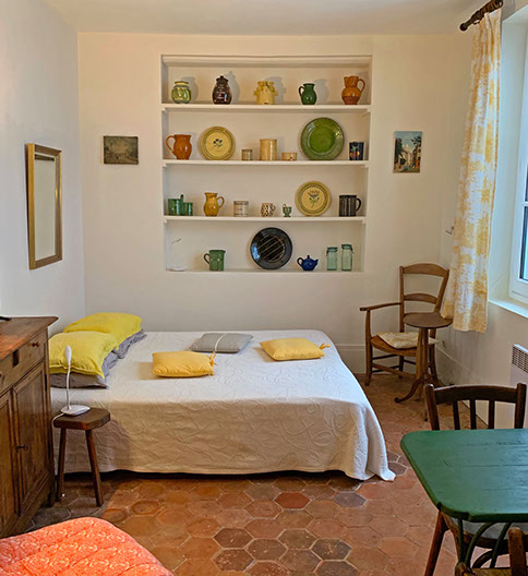 Studio interior with shelves of pottery, queen bed, mirror, armchair and small oval table, green dining table, bistro chairs.