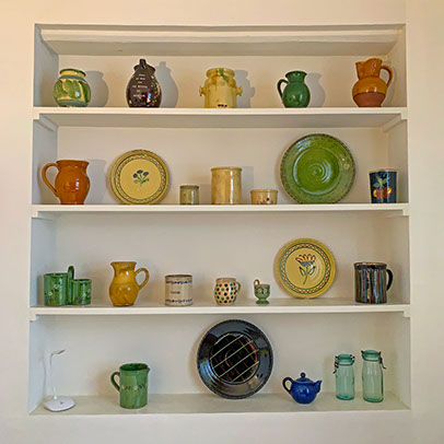 Beautiful pottery on shelves.